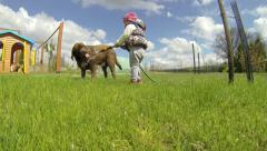 Little Girl Playing with sprinkler and washing a dog - stock footage