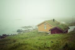 Houses with typical sod roof on lofotten islands in norway Stock Photos