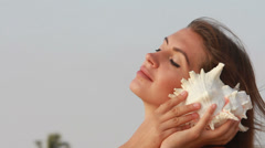 Beautiful woman listening shell. - stock footage