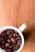 cup full of coffee beans - stock photo