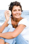 woman on seacoast with a cockleshell in hands - stock photo