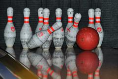 Bowling ball hits pins - stock photo