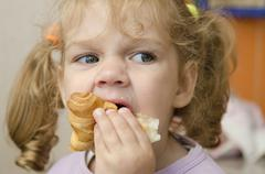 Little girl with enthusiasm and eats roll pleasure Stock Photos