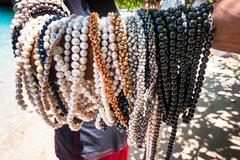 vendor necklaces of pearls, sumbawa, komodo island,   indonesia - stock photo
