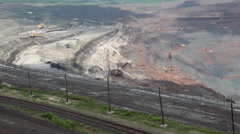 Heavy equipment digs and hauls ore inside an enormus open pit mine Stock Footage