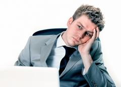 exhausted businessman at the office - stock photo