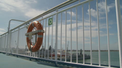 Curve dolly ferry railing through port in UK Stock Footage