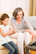 Grandmother teach young girl play flute happy - stock photo