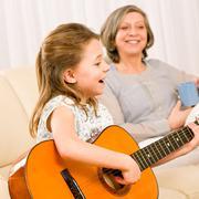 Young girl sing play guitar to grandmother Stock Photos