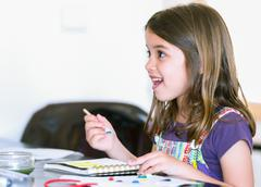 Expressive portrait of a pretty young girl doing paint Stock Photos