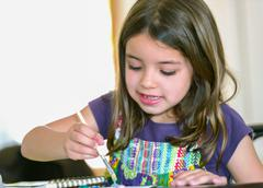 Portrait of lovely girl drawing with colorful pencils Stock Photos