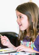 expressive portrait of a pretty young girl doing paint - stock photo