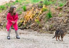 little girl afraid of a cat - stock photo