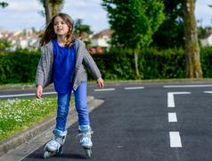 Pretty little girl doing rollerblade in the street Stock Photos