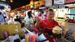 Tourist buy a fresh coconut water on Khao San Road in Bangkok, Thailand. - stock footage