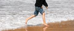 young boy running feet ocean beach surf crashing sea foam - stock photo