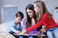 Young mom play with their kids at home and reading book Stock Photos
