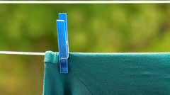 Green clothes hanging to dry on laundry line Stock Footage