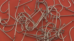 Large sea angling, fishing hooks rotating on a red background. Stock Footage