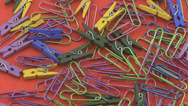 Stock Video Footage of Assorted coloured  paper clips rotating on a red background.