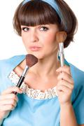 Brunet woman with two make-up brushes Stock Photos