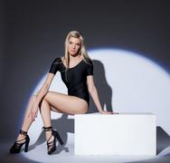 Attractive leggy blonde posing in spotlight - stock photo