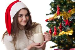 Teenage girl with coffee mug under Christmas tree - stock photo