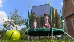 Mom and little girl play and jump on Trampoline. Country House Yard. Stock Footage