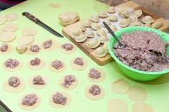 Rolling pin, dough and raw pelmeni Stock Photos