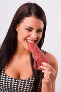 beautiful brunette woman bites raw red steak meat eater - stock photo