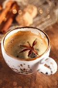 A cup of spiced coffee with anis star and cinamon sticks and sug Stock Photos