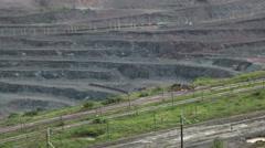 Heavy equipment digs inside huge open pit mine Stock Footage