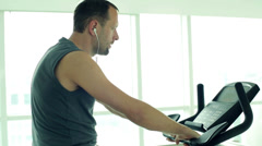young man ride a stationery bike at the gym HD - stock footage