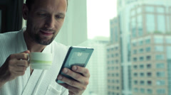 Young man drinking coffee and using smartphone by the window with the cityscape Stock Footage