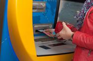 Stock Photo of Woman withdrawing cash at a bank ATM
