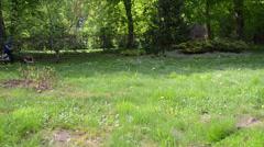 Gardener man worker cut grass with lawn cutter arround trees Stock Footage