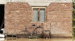 Cinematic look. Old bike leaning on wall of the unfinished building after flood. Stock Footage