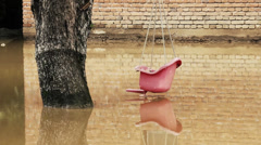 Cinematic look. Pink swing for children hanging on the tree in flooded backyard. Stock Footage