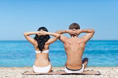 Couple on beach sunbath tanning, rear view - stock photo