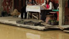 River flooded unfinished yard. Grandmother and granddaughter sitting on terrace. Stock Footage
