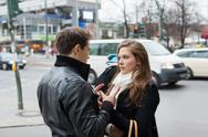 Stock Photo of Couple In Jackets Communicating On Street Side