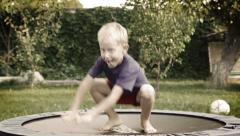 Cheerful blond boy jumping on trampoline in the summer garden Stock Footage