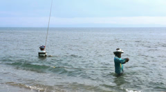 Local fisherman standing in the sea, Lombok Island, Indonesia, Asia Stock Footage