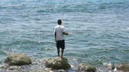 Stock Video Footage of Local fisherman standing in the sea, holding a fishing rod to catch fish, Lombok