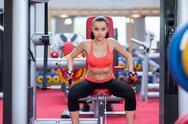 Stock Photo of Woman exercising arms gym machine