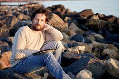 Smiling man with tablet on beach with rocks Stock Photos