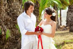 bride and groom near palm-tree - stock photo