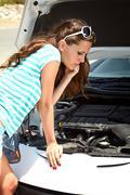 Woman is standing near broken car Stock Photos