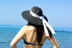 Stock Photo of woman looking horizon with hat in front of beautiful blue sea