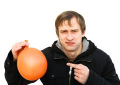 dissatisfied young man hold a balloon which is blown off - stock photo